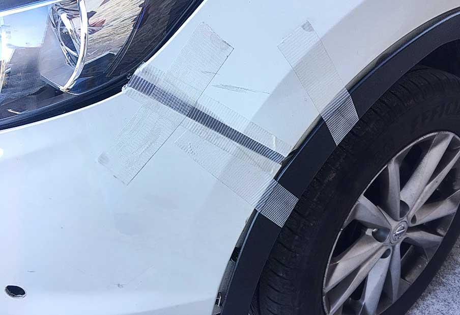 Reparando el parachoques del coche con cinta americana transparente