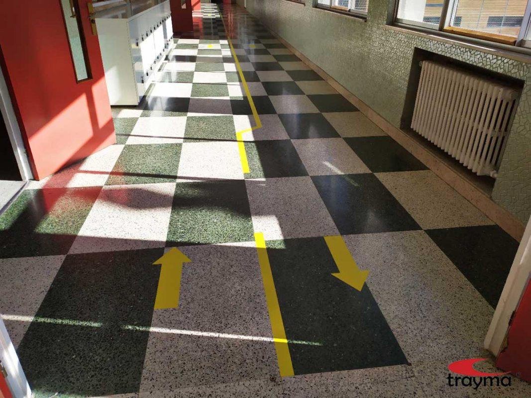 Señalización pasillos colegio con flechas que indican el sentido de la marcha